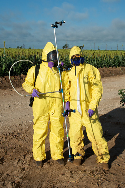 Getting suited up to spray miticides on corn research plots. The protective equipment is very hot to wear; safety from the chemicals vs. the risk of heat stroke.
