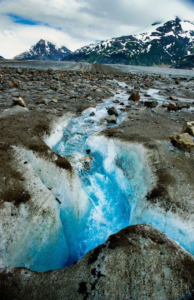 Summer melt water disappearing into a crevasse, Meade Glacier near Skagway Alaska