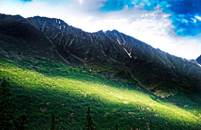 Narrow strip of sunside, late evening early July, bisects a mountain near the Nenanna River, Denali Naitonal Park