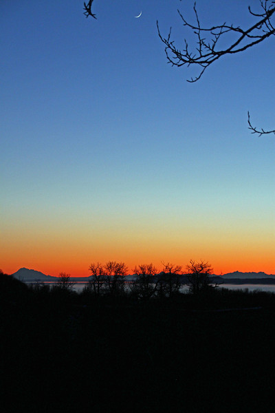 3.02.14: After working all night and then sleeping most of the day I managed to drag myself out of bed and around town for a few photographs ending the day with this sunset as seen from Kincaid Park looking out over Cook Inlet to the Alaska Range, the crescent moon was a bonus.