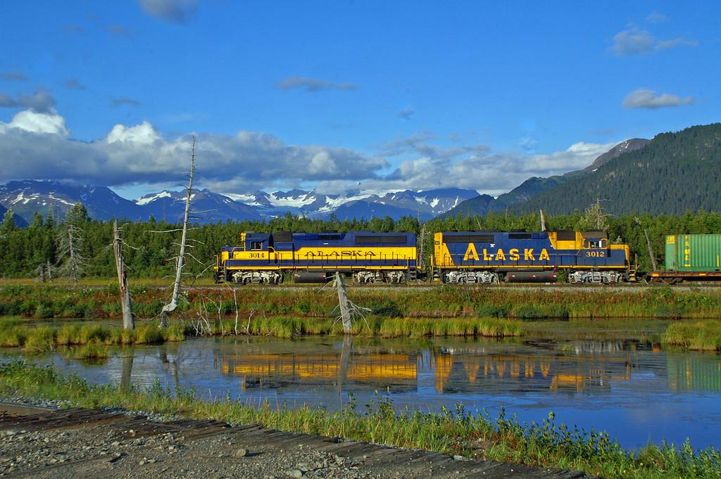 A saltwater pond reflects an Alaska Railroad train near Portage, Alaska.