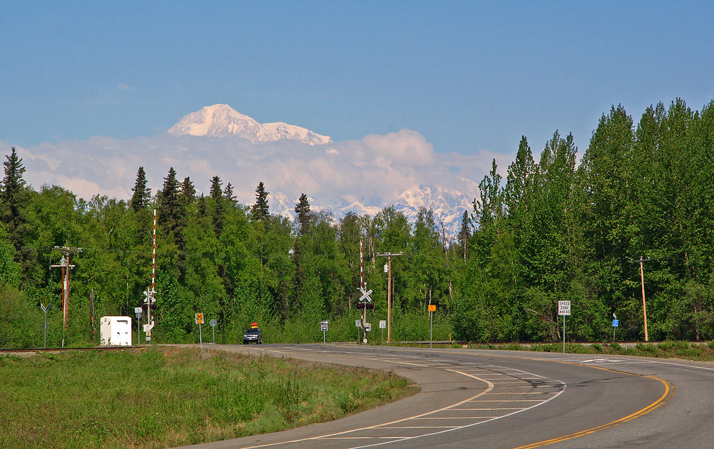 Denali peeks above the clouds as seen from the Parks Highway in Talkeetna, Alaska.