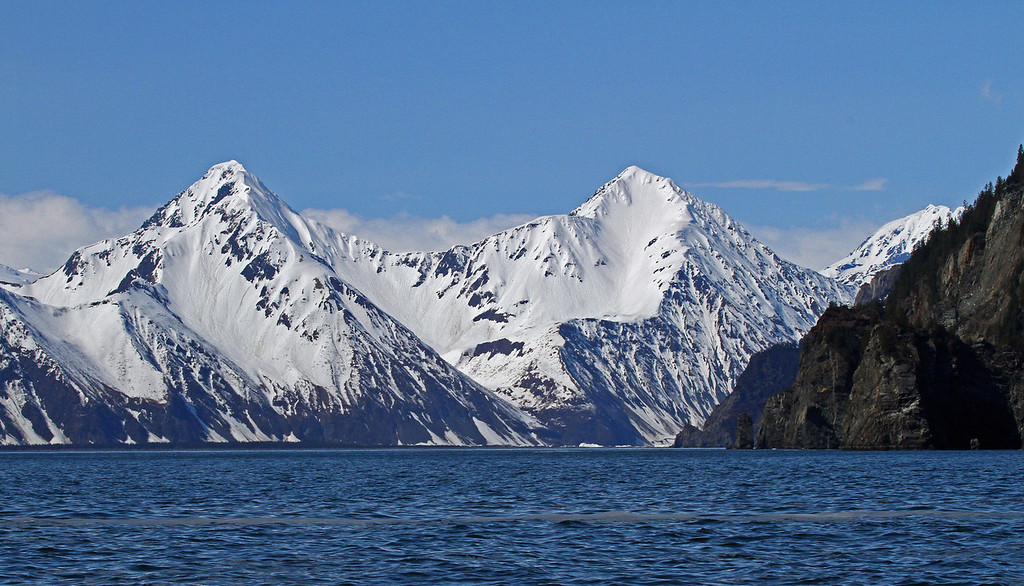 The blue waters of Resurrection Bay contrast nicely with the surrounding white capped mountains.