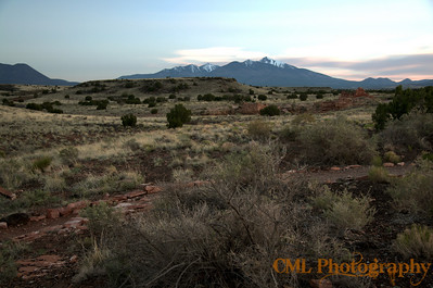 Looking out over the Colorado Plateau and the Box Canyon Ruins in Wupatki National Monument at sunset.  The San Francisco Peaks are in the distance.  A lot of the rounded hills you see on the horizon are old cinder cones.