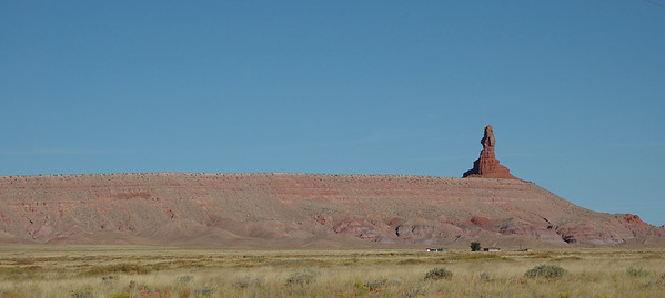 "On the road from Kayenta heading north east, you get an interesting pair of markers. A Navaho version of the ""Pillars of Hercules"", perhaps. This is on the north side. One can only wonder how the spire has survived while the rest of the rock washed away.  The photo comes from a panoramic crop of a single picture. No other photo manipulation here."