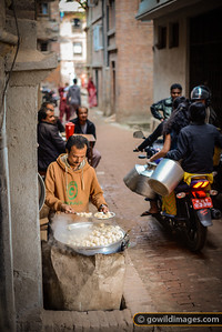 Locals enjoy fresh momos straight from the steamer as a family passes by on motorbike to fetch water from the nearby well