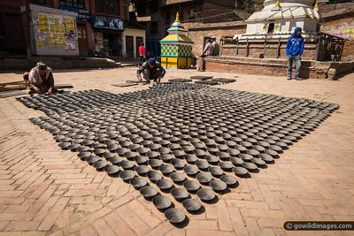 Handmade pottery bowls, laid out to dry in the sun