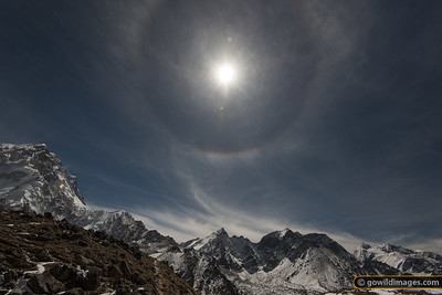A '22 degree halo' above Nuptse. This rare phenomenon occurs when there are thin cirrus cloud containing hexagonal ice crystals. The spots just above and below the sun are lens flare, but the colour fringe and darker inner circle are part of the halo effect and are not introduced by the photography process.