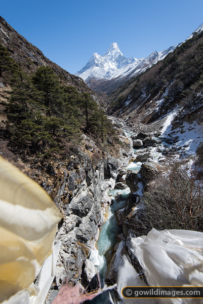 Prayer flags flutter on a high bridge, with a view to Ama Dablam