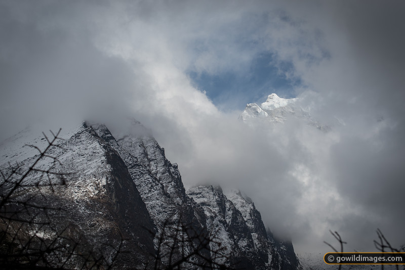 Transient view of high peaks peeking through the clouds
