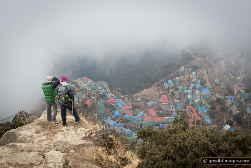 A local guide and a tourist enjoy the view down to Namche, along the trail to Syangboche