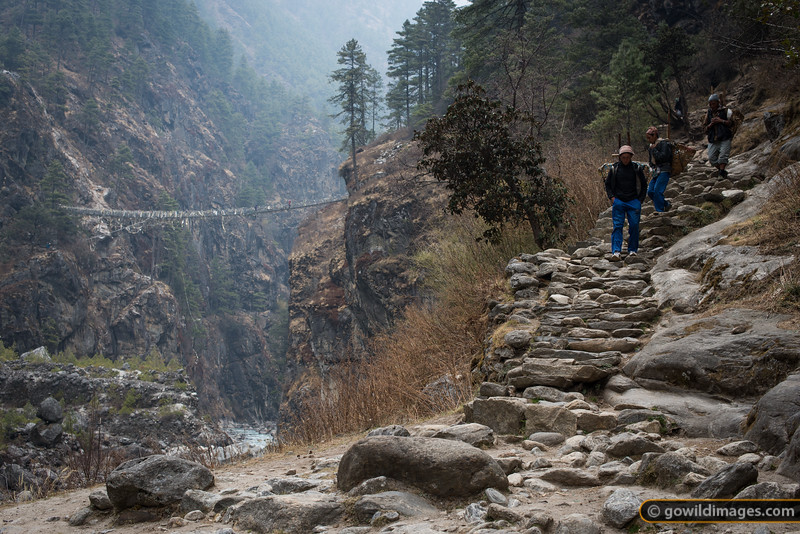 Porters head through Jorsale to the Namche market. A suspension bridge swings high above the Dudh Kosi.