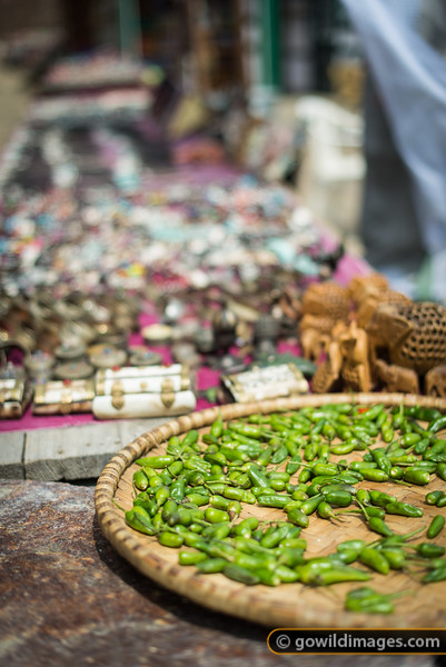 Chillies drying in Kyangjuma, with Tibetan craft trinkets on sale beside