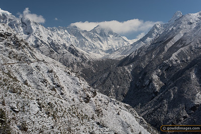 A stupa under snow (left) on the trail to Tengboche monastery (centre). Mt Everest (8850m) is making clouds just left of centre, with Lhotse (8516m) partly obscured just to the right. Far right is Ama Dablam peak.