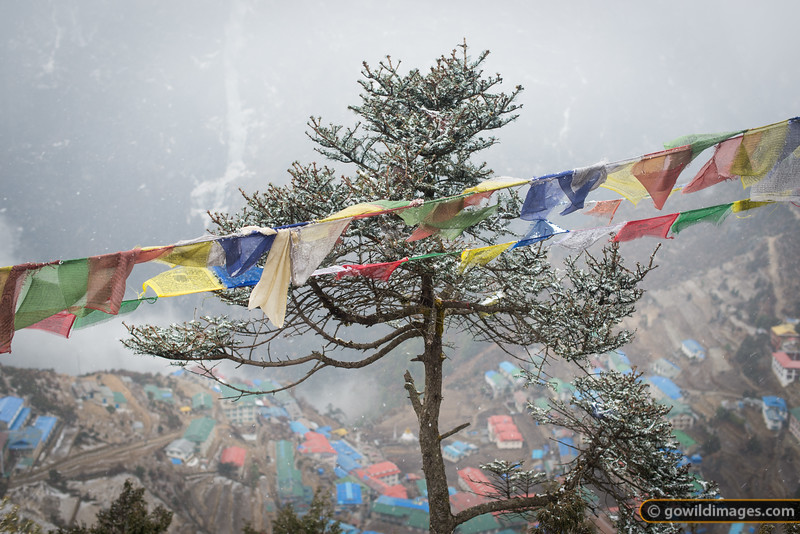 Prayer flags decorate the view down to Namche, along the trail to Syangboche after light Spring snows