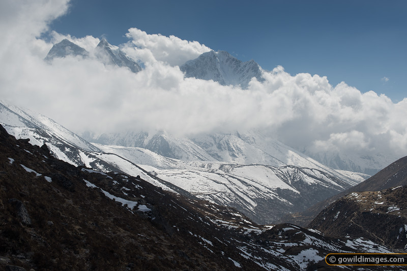 Afternoon clouds, typical of Spring, begin to move up the valley and obscure Kangtega (left) and Thamserku (right). The main EBC trail can be seen in the lower right.