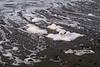 Foam flecks, storm residue left by the tide