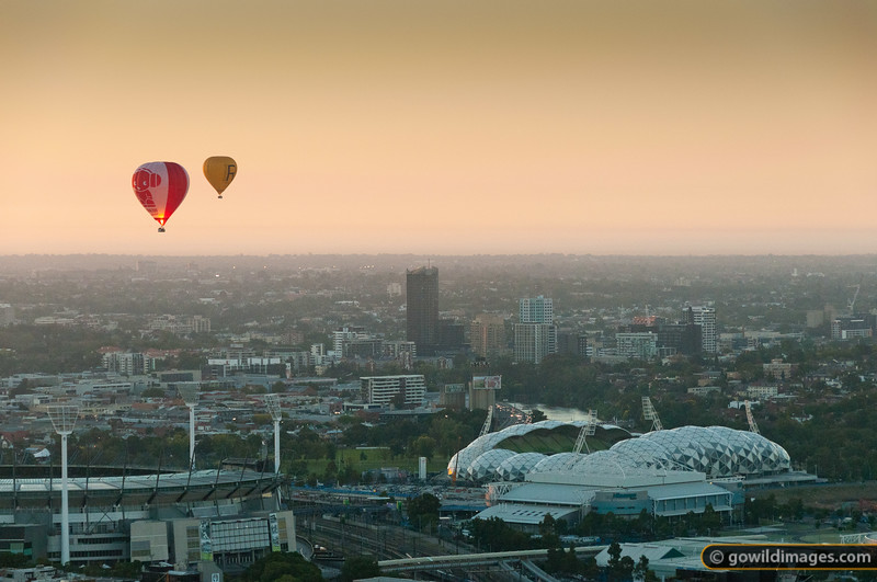 Hot air balloons after sunrise over the Melbourne Cricket Ground (left) and AAMI Park (right)