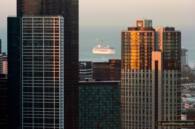 Early morning sun on Crown Casino and Sheraton Towers with Tasmanian ferry in Port Phillip Bay behind