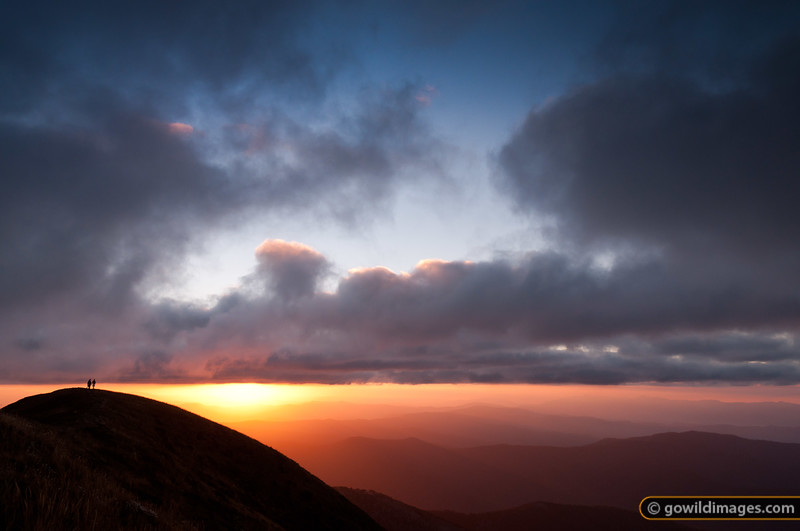 Hikers on the summit of Mt Feathertop at sunset, Mt Buffalo in the distance (right)