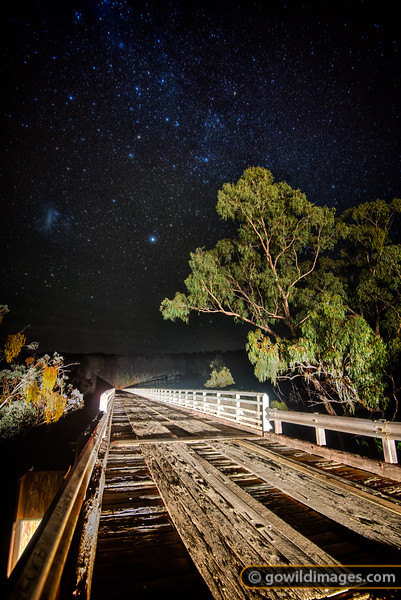 The Greater Magelannic Cloud is the only cloud in the sky on a cold Winter night at McKillops Bridge, Snowy River NP. With a 255m span – the longest metal-truss, wooden bridge in the state, first built in 1931 and rebuilt in 1936 after a flood [201712. Featured in Behind the Wheel book]