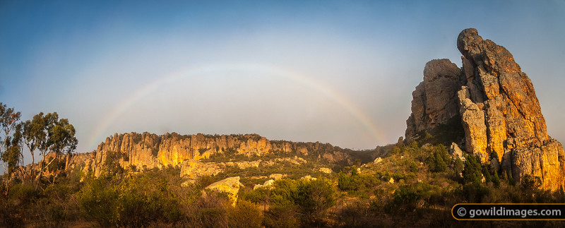 Early morning rainbow forms above Mt Arapiles as the light mist begins to lift. 'The Bluffs' are central and 'Bard Buttress' – the popular 120m grade 12 climb – is the tower on the right. Other angles available.