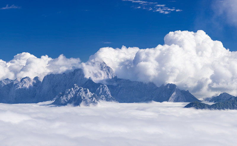 Nel fondovalle c'è la grigia nebbia, ma sopra i 1700 metri, questa appare come un luminoso mare di nubi bianche. <br /> Al centro il monte Mangart. <br /> <br /> Foto n° 011013-886199 #CX