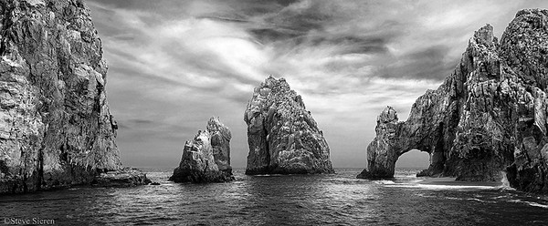 Lover's Arch Panoramic black and white Los Cabos, Baja California Sur, Mexico (AKA Cabo)   Being foregroundless is not something I usually do but from the second level of a boat I didn't have much of a choice. I also took a few panos from a kayak the day before. Guessing on more sharpness from the boat though. My girlfriend was too scared to get a little closer to arch in the kayak. You can't see him but there is a kayaker to the left of the 1st middle seastack. I'm still using the D70 as a backup because I don't want to risk taking my 5D underwater and now shooting with the Mark II.   F9 1/125 sec iso 200  18-70mm nikkor D70 PL filter