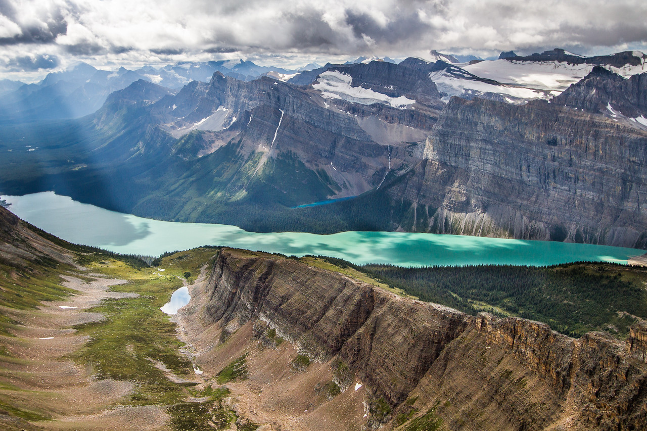 Standing on Bow Peak above a classic U shaped glacial valley leading to 2 stunning lakes: Hector lake and Lake Margaret behind.