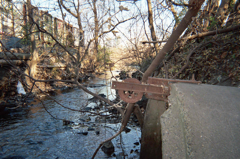 A large storm sewer outlet on south side of creek. I do not know the function of the pully mounted on the pipe. Pioneer Paper property on left.<br /> Downstream view.<br /> Photo by Dave Stack.