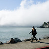 A pedestrian walking through Sausalito on a foggy summer morning.