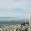 Rooftop view of San Francisco with Alcatraz shrouded in fog, Coit Tower and, in the foreground, the famous Transamerica Pyramid.