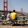 A couple of bikers (a biker couple?) enjoying the view at an overlook near the Golden Gate Bridge.