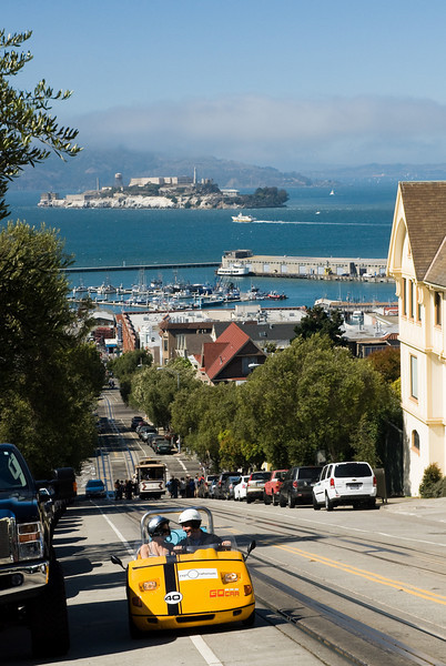 """Uphill """"GoCar"""" ride on Hyde Street, with Alcatraz in the background."""