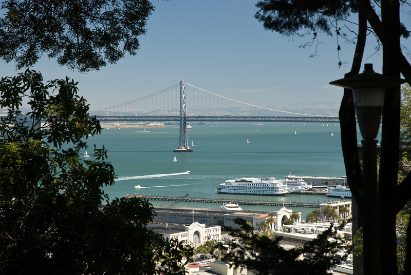"A boat racing past steamboat ""California Hornblower"" towards the Bay Bridge."