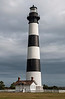 "Bodie Island Lighthouse. This photo was taken just after a thunderstorm had passed. The lighthouse is illuminated and the clouds remain behind it as a nice contrast. This photograph was taken when the lighthouse was still active and shined nightly. The ""repairs"" of 2010-current day have left the light with a new coat of paint but non-operational."