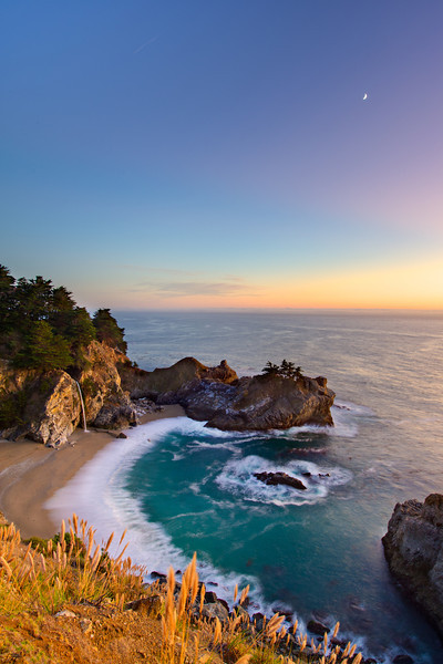 """McWay Falls at Sunset""  Nestled just south of Big Sur, this amazing waterfall is located just off the highway and spills into the Pacific Ocean.  I am amazed how many people visit the San Francisco Bay Area and even Big Sur and STILL have never been to see McWay Falls and Julia Pfeiffer Burns State Park!  I managed to get down to McWay Falls at Sunset after shooting around Big Sur to find this sliver of a moon in the sky right at dusk. This is a another great place to visit along the Northern California coastline - I often find folks make it to Big Sur but don't drive the extra 30 minutes to visit this awesome falls!!!"