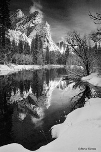 The Three Brothers reflect in the moring glass of the Merced River in Yosemite Valley.
