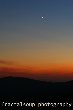 Crescent Moon in Sky above colorful Mountain Sunset