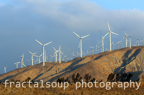 Wind Turbines  at work on a hill against a blue clouded sky