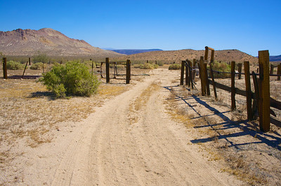 Dirt Road Leads into Wooden Corral