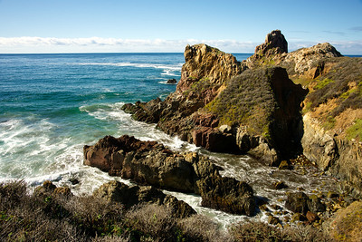 Rock formations jutting into the Pacific Ocean along the Pacific Coast Highway.