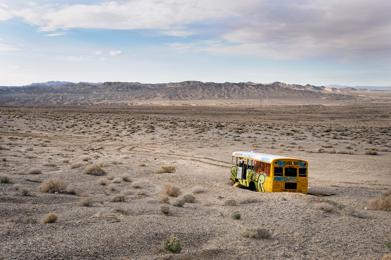 An abandoned, graffiti riddled school bus has found its resting place in a desolate region of the Mojave desert.