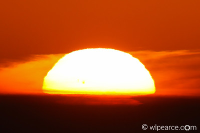 800mm shot of clear sunset.  The three dark spots just to left of center near horizon are sunspots.