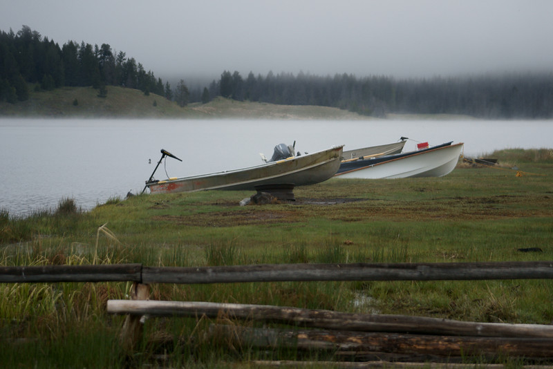 Boats on shore of the foggy lake.