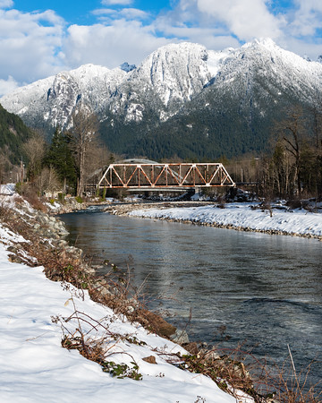 Snowy Cascade Mountains towering over the Index rail bridge in Winter