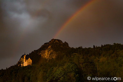 Neuschwanstein in a storm underlit by the setting sun.