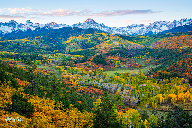 "Near Ridgway, Colorado<br /> First Light on the San Juan Range<br /> Time of Day:  Morning Twilight<br /> Date:  October 3, 2013<br /> <br /> Having seen several images of this general location over the past few years I must admit:  I simply love this view.  And so getting a decent shot of this scene became important to me.  See Jack Braur's rendition  at <a href=""http://www.mountainphotography.com/photo/sneffels-range-autumn/"">http://www.mountainphotography.com/photo/sneffels-range-autumn/</a> as a classic example.<br /> <br /> Back in 2012, Casse and I shot this area to no avail, but I learned from the experience that the scene does not lend itself well to photography with direct sunlight upon it; diffuse light works best.  We met painter Jay Moore who was there painting while we were photographing in 2012.  See <a href=""http://www.jaymoorestudio.com/portfolio/mount-sneffels/"">http://www.jaymoorestudio.com/portfolio/mount-sneffels/</a> for Jay's rendition.<br /> <br /> It turns out that there is a ""secret ingredient"" in the recipe (of course).  You have to climb down the hill to get around the foliage blocking an unobstructed, expansive view.  <br /> <br /> Dauuhhh!<br /> <br /> Well, thankfully, I did some midday reconnaissance a couple of days beforehand and happened upon an Ol' Timer who, upon inquiry, told me about this trail leading down the hill.  I asked about snakes and bears and he said the snakes are non-venomous (snake phobia here!) and the bears, though rarely seen, are brown bears and generally won't bother you unless you scare 'em (don't wanna be no bear's breakfast either!).  Upshot:  sing or carry a bell and you'll be OK.<br /> <br /> So I set out about an hour before sunrise and went down the hillside, with my headlamp blazing, to a pre-scouted site while singing ""Wildfire,"" rather ineptly, I might add:   <br /> <br /> ""She comes down Yellow Mountain, on a dark flat land she rides, on a pony she named Wildfire, with a whirlwind by her side, on a cold Nebraska night…."" – Michael Martin Murphey<br /> <br /> Can you see the cows grazing below?<br /> <br /> A two stop hard grad was used in this shot."