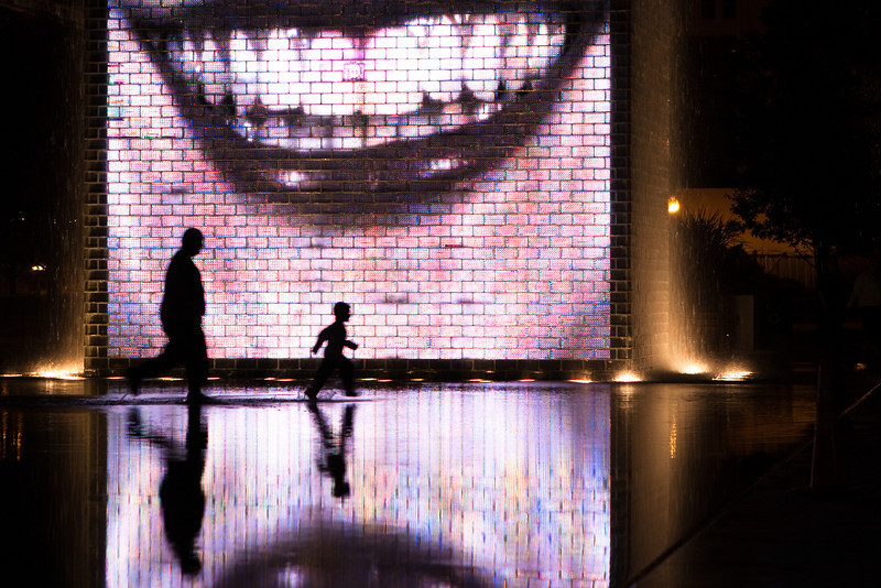 A boy and his dad having fun in the water at Crown Fountain.