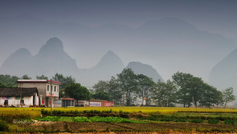 Limestone peaks loom in the everpresent haze, Jiantou Village